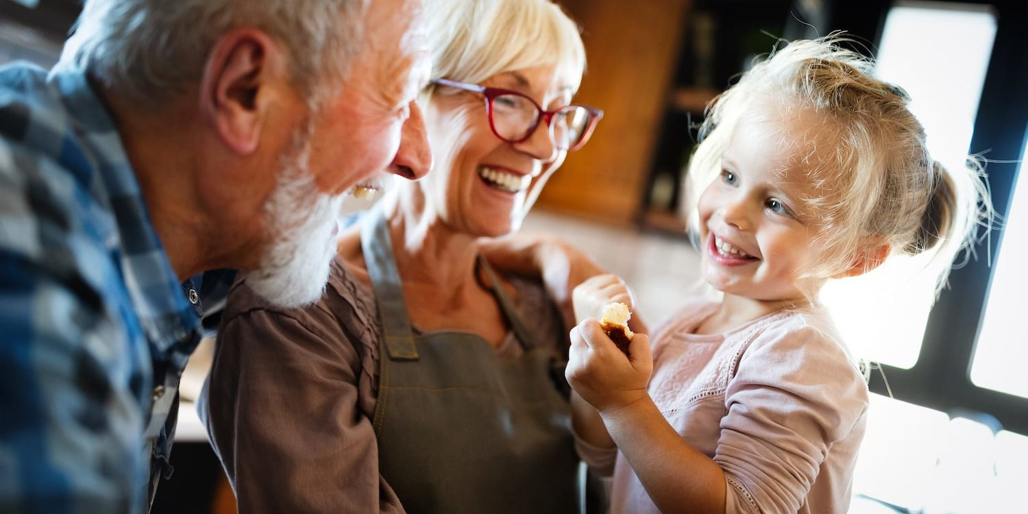 Happy smiling grandparents having fun times with children at home